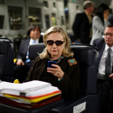 U.S. Secretary of State Hillary Clinton checks her PDA upon departure in a military C-17 plane from Malta bound for Tripoli, on October 18, 2011.  AFP PHOTO/KEVIN LAMARQUE/POOL (Photo credit should read KEVIN LAMARQUE/AFP/Getty Images)