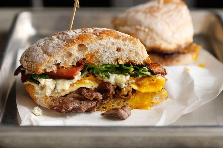 Bistec: Flat-iron Angus steak, smoked bacon, blue cheese, caramelized onions, baby spinach, sun-dried tomato vinaigrette, ciabatta roll.
