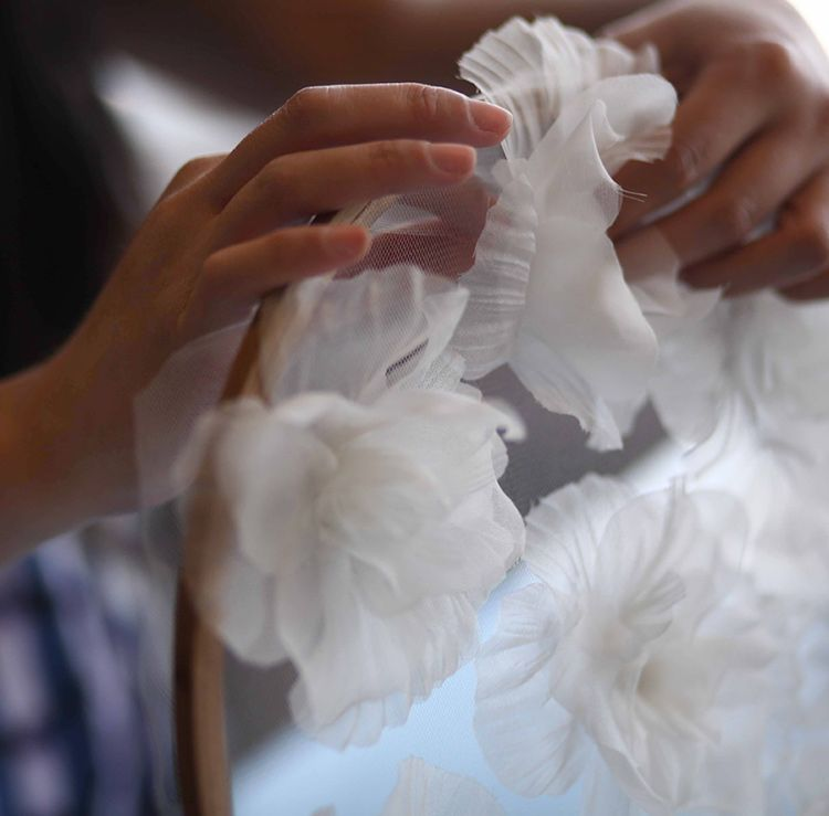 Woman attaches fabric flowers to a dress form