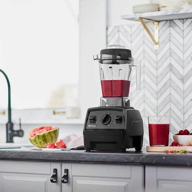 black vitamix blender with red watermelon smoothie inside, sitting on kitchen countertop - strategist best blender for smoothies