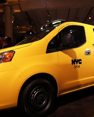People look at the new New York City taxi which is designed by the Nissan Motor Co. at an official unveiling on April 3, 2012 in New York City. The new taxis, which will start appearing on the streets of New York next year, service an estimated service 600,000 people daily. The 2014 NV200 Taxi will replace the fleet of iconic Ford Crown Victorias, Ford Escape Hybrids and Toyota Siennas that are currently being used. Some of the highlights of the new taxi include front and rear-seat occupant curtain airbags, a window on the roof, backseat cellphone charging and USB ports and passenger reading lights. (Photo by Spencer Platt/Getty Images)
