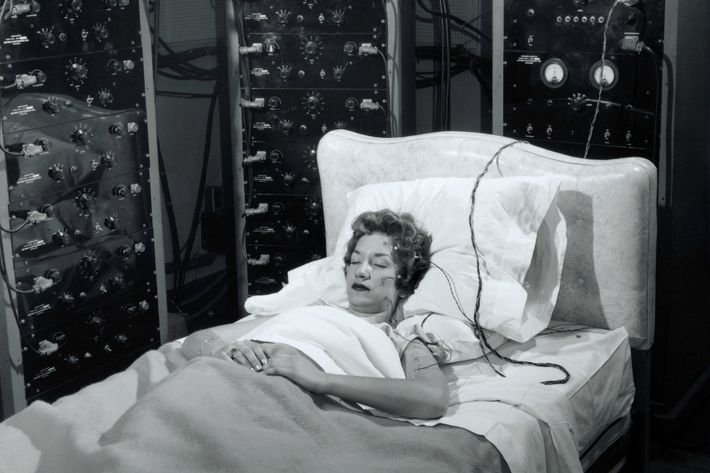 A woman sleeps in a bed surrounded by electronic monitoring equipment.