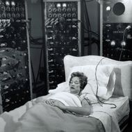 Woman sleeping with electrodes on head.