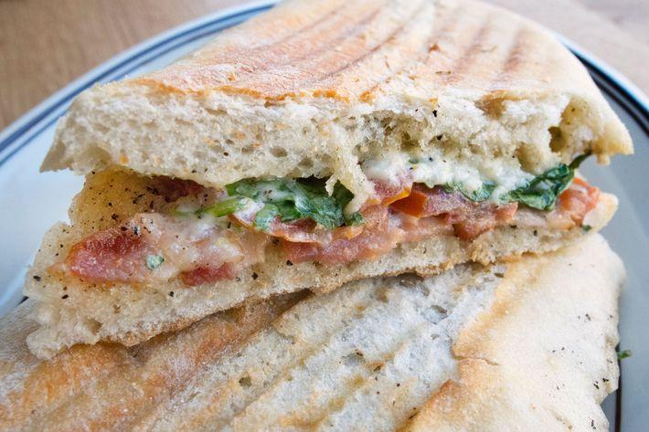 Smoked-bacon panino with tomato, arugula, and Asiago.