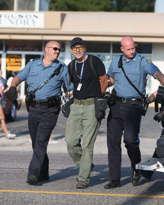 FERGUSON, MO - AUGUST 18: Getty Images staff photographer Scott Olson is placed into a paddy wagon after being arrested by police as he covers the demonstration following the shooting death of Michael Brown on August 18, 2014 in Ferguson, Missouri. Protesters have been vocal asking for justice in the shooting death of Michael Brown by a Ferguson police officer on August 9th. (Photo by Joe Raedle/Getty Images)