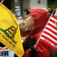 """CHICAGO, IL - APRIL 16:  Kay Herrmann sings the National Anthem at the start of a Tea Party rally which was held to protest President Barack Obama's proposed """"Buffett rule"""" tax plan on April 16, 2012 in Chicago, Illinois. The tax plan, which will be voted on today, would impose a minimum tax on wealthy Americans.  (Photo by Scott Olson/Getty Images)"""