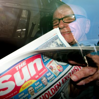 "News Corporation Chief Rupert Murdoch holds up a copy of the newly launched 'The Sun on Sunday' newspaper as he leaves his London home on February 26, 2012.  Rupert Murdoch's Sun on Sunday tabloid hit news stands on Sunday, replacing the defunct News of the World with a pledge to meet high ethical standards after a ""challenging"" chapter in its history. AFP PHOTO/CARL COURT (Photo credit should read CARL COURT/AFP/Getty Images)"