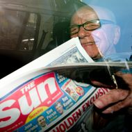 News Corporation Chief Rupert Murdoch holds up a copy of the newly launched 'The Sun on Sunday' newspaper as he leaves his London home on February 26, 2012. Rupert Murdoch's Sun on Sunday tabloid hit news stands on Sunday, replacing the defunct News of the World with a pledge to meet high ethical standards after a