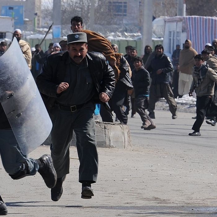 Afghan policemen run from the crowd during clashes with protestors demonstrating against Koran desecration in Kabul on February 23, 2012. The Taliban exhorted Afghans on February 23 to attack and kill foreign troops to avenge the burning of Korans at a US-run base, but stopped short of cutting off contacts with American officials in Qatar. AFP PHOTO/SHAH Marai (Photo credit should read SHAH MARAI/AFP/Getty Images)