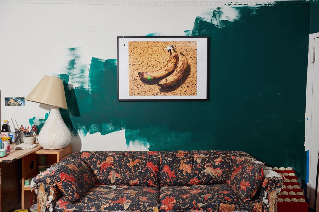 A room with a partially painted teal-green wall, a red-and-black paisley print sofa, a photograph of a ripe banana hanging on the wall, and the corner of a desk with jars of paint brushes and a table lamp with a tilted shade.