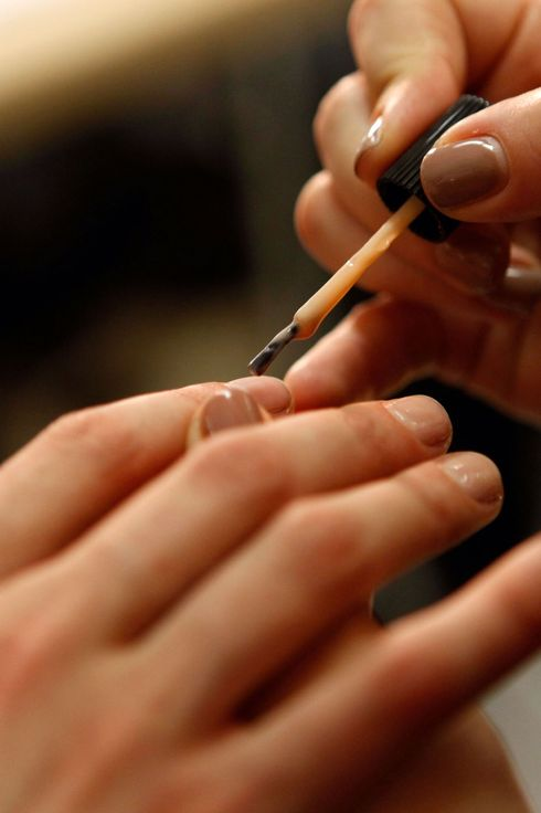 A manicurist paints a models nails backstage at the Band of Outsiders Spring 2013 fashion show for butter LONDON during Mercedes-Benz Fashion Week at St John's Center on September 8, 2012 in New York City.
