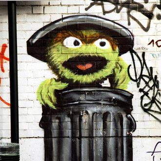 London, England, UK --- Urban Grafitti, East London - Seasame Street style Monster (Oscar the grouch) in a bin.