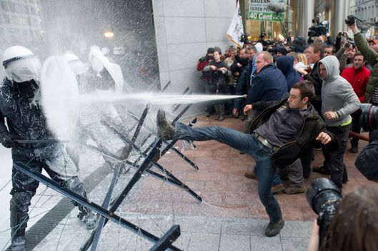 Police officers, left, are sprayed with milk by European milk farmers during a demonstration outside the European Parliament in Brussels on Monday, Nov. 26, 2012. Farmers drove their tractors into the European Quarter of Brussels on Monday for a two-day demonstration to protest against what they believe are unfair milk prices.