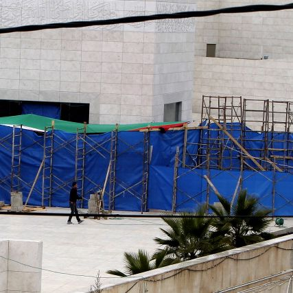A Palestinian worker walks with a water hose in front of the tarpaulin hiding the mausoleum of the later Palestinian leader Yasser Arafat, on November 27, 2012, at the Muqataa in the West Bank city of Ramallah. The remains of iconic Palestinian leader Yasser Arafat were exhumed and experts began taking samples to be tested for signs of poisoning, Palestinian sources told AFP. AFP PHOTO/AHMAD GHARABLI