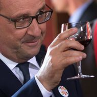 French President Francois Hollande raises a glass for a toast during a Tastevin confraternity induction ceremony at the Chateau Clos Vougeot, in the Burgundy wine region