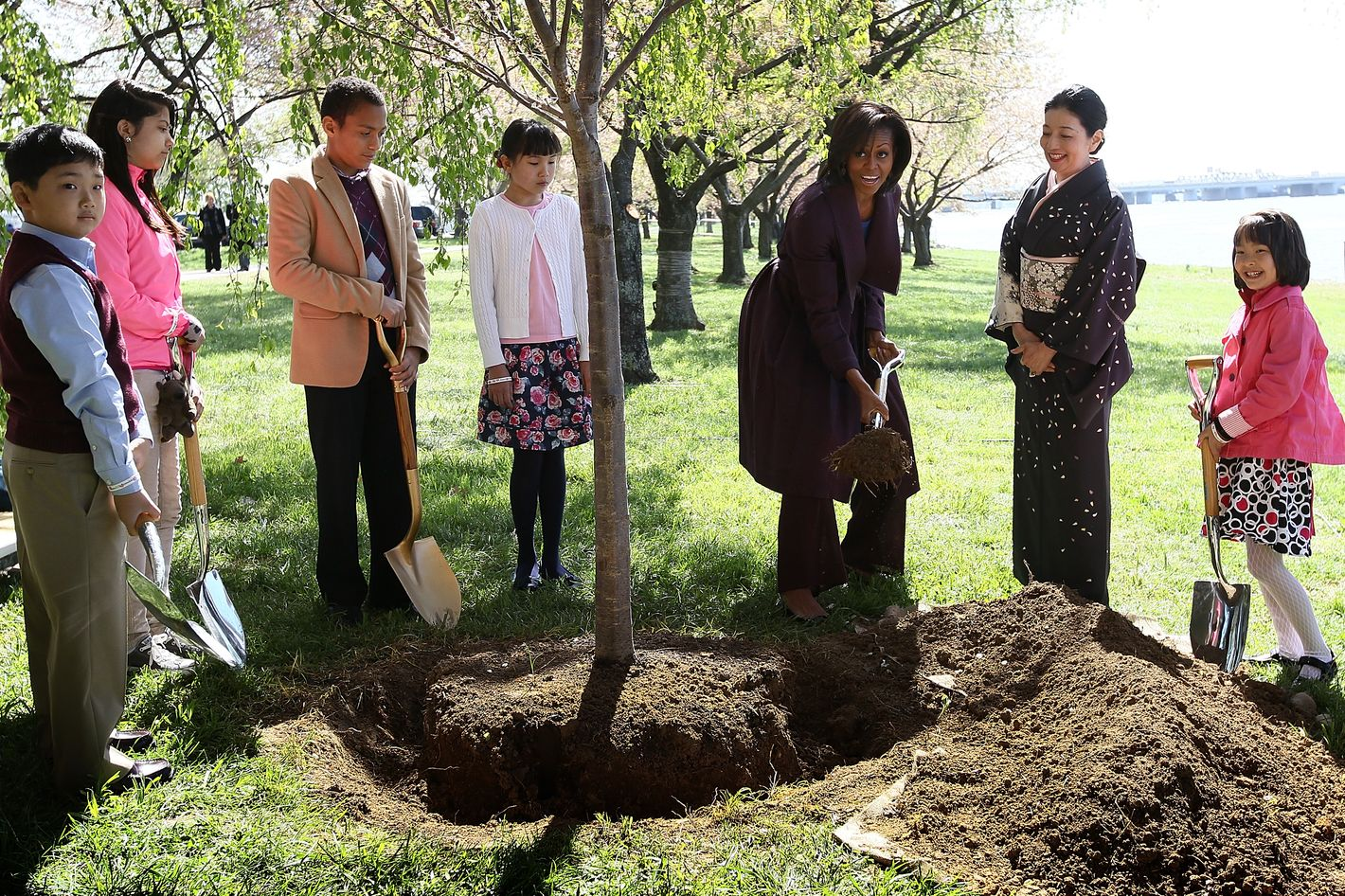 WASHINGTON, DC - MARCH 27:  U.S. first lady Michelle Obama (3rd R) takes part in a 1912 Cherry Blossom tree planting re-enactment ceremony with Yoriko Fujisaki (2nd R) near the Tidal Basin and along the Potomac River March 27, 2012 in Washington, DC. 2012 marks the 100th anniversary since the United States received 3,000 Cherry Blossom trees as a gift from Japan symbolizing the friendship between the two countries.  (Photo by Win McNamee/Getty Images)