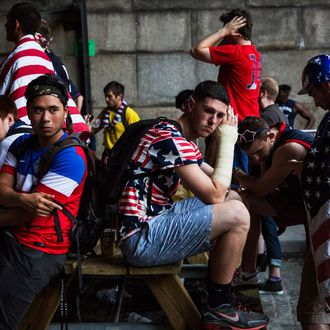 NEW YORK, NY - JULY 01: Fans sit in defeat after the United States lost to Belgium in the World Cup under the Manhattan Bridge on July 1, 2014 in the Dumbo neighborhood of the Brooklyn borough of New York. Belgium eliminated the U.S. from the World Cup in overtime with a final score 2-1. (Photo by Andrew Burton/Getty Images)