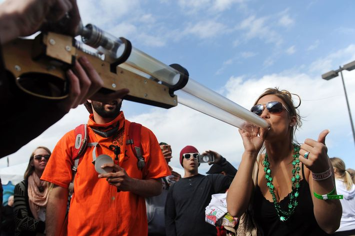 DENVER, CO - APRIL 19: Kimberly Bullard, 23, of Los Angeles, California takes a hit off a I420 Double Barrel Shotgun pipe during the High Times Cannabis Cup at the Denver Mart in Denver, Colorado on April 19, 2015. The High Times Cannabis Cup runs through Monday at the Denver Mart. (Photo by Seth McConnell/The Denver Post via Getty Images)