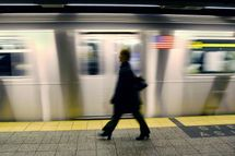 A woman walks along the platform as a number 6 train of the New York City subway passes by 13 December, 2002, at Grand Central Terminal in New York. The 34, 000 member Transit Workers Union is threatening a strike if their contract with the Metropolitan Transit Authority expires at 12:00 AM, 16 December, shutting down subway and bus service across the city.
