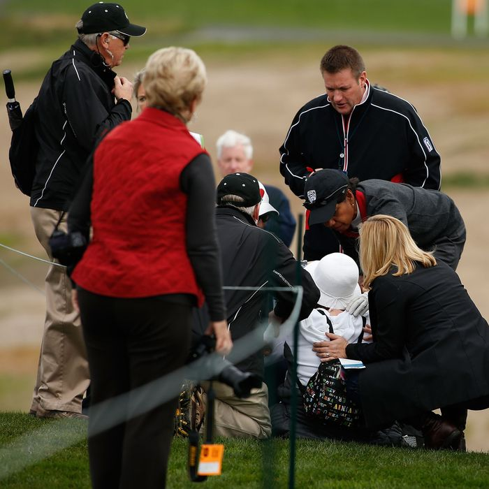 Former Secretary of State Condoleezza Rice (C) checks on the fan she struck with her golf ball on the sixth hole during the first round of the AT&T Pebble Beach National Pro-Am at Pebble Beach Golf Links on February 7, 2013 in Pebble Beach, California.