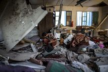 "A Palestinian scout collects human remains from a classroom inside a UN school in the Jabalia refugee camp after the area was hit by shelling on July 30, 2014. Israeli bombardments early on July 30 killed ""dozens"" of Palestinians in Gaza, including at least 16 at a UN school, medics said, on day 23 of the Israel-Hamas conflict."
