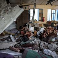 """A Palestinian scout collects human remains from a classroom inside a UN school in the Jabalia refugee camp after the area was hit by shelling on July 30, 2014. Israeli bombardments early on July 30 killed """"dozens"""" of Palestinians in Gaza, including at least 16 at a UN school, medics said, on day 23 of the Israel-Hamas conflict."""