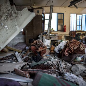 A Palestinian scout collects human remains from a classroom inside a UN school in the Jabalia refugee camp after the area was hit by shelling on July 30, 2014. Israeli bombardments early on July 30 killed