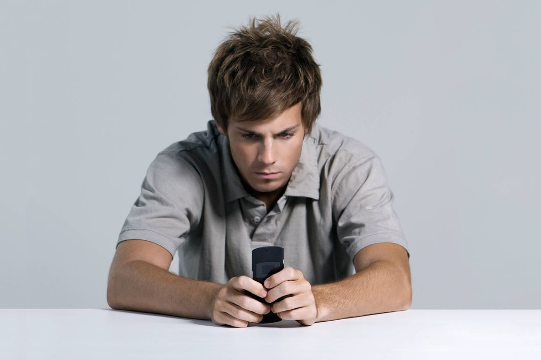 Young man text messaging with cell phone, furrowing brow --- Image by ? Matthieu Spohn/?s/Corbis