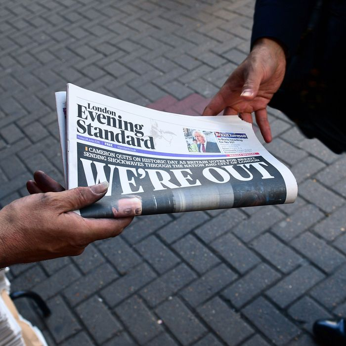 A man takes a copy of the London Evening Standard with the front page reporting the resignation of British Prime Minister David Cameron and the vote to leave the EU in a referendum, showing a pictured of Cameron holding hands with his wife Samantha as they come out from 10 Downing Street, in London on June 24, 2016.