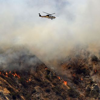 A water-dropping helicopter flies over burning hills in Azusa, California, northeast of Los Angeles, June 20, 2016 amid fires as temperatures in the region reach triple digits.