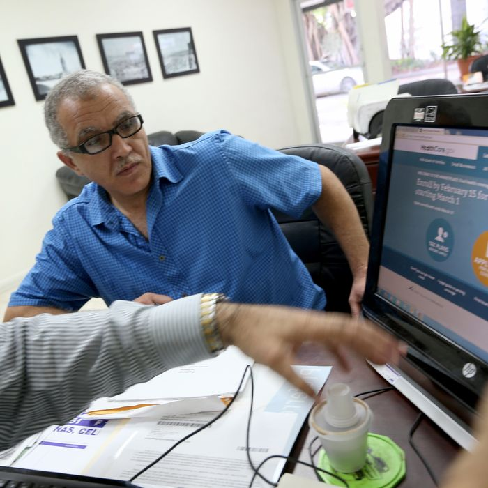 MIAMI, FL - FEBRUARY 13: Hisham Uadadeh enrolls in a health insurance plan under the Affordable Care Act with the help of A. Michael Khoury at Leading Insurance Agency on February 13, 2014 in Miami, Florida. Numbers released by the government showed that about 3.3 million people signed up for health insurance plans under the Affordable Care Act through the end of January. (Photo by Joe Raedle/Getty Images)