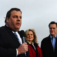 Republican presidential hopeful Mitt Romney (R) and his wife Ann Romney look on as New Jersey Governor Chris Christie speaks during a campaign rally outside a grocery store in Des Moines, Iowa, on December 30, 2011