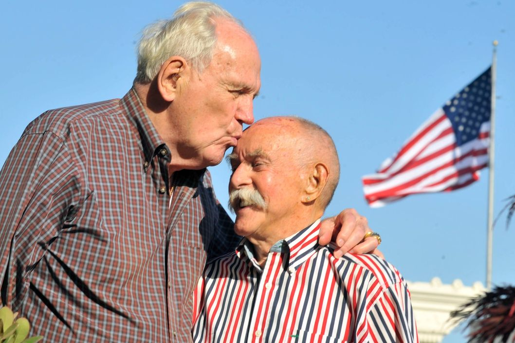 John Darby (L) kisses his husband Jack Bird (R) at their home in San Francisco, California on May 02, 2013. This year, the couple will celebrate 54 years of being together and five years of marriage.