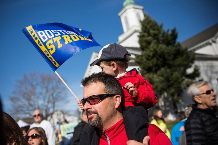 HOPKINGTON, MA - APRIL 21:  A father carrying his son on his shoulder watches the scene at the starting line of the Boston Marathon on April 21, 2014 in Hopkington, Massachusetts. Today marks the 118th Boston Marathon; security presence has been increased this year, due to two bombs that were detonated at the finish line last year, killing three people and injuring more than 260 others.  (Photo by Andrew Burton/Getty Images)