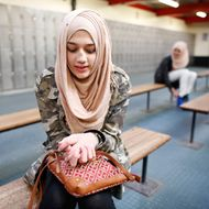 """Ameera, 12, waits to go ice skating in east London March 8, 2014. Ameera first wore the hijab as part of her primary school uniform. She started to wear it full time age 9 because most of her friends wore the hijab. Her mother would tell her """"You don't have to wear it. You're still young!"""" She loves to wear the hijab and has as many as 60 or 70 different scarves. Reuters photographer Olivia Harris took portraits of a range of Muslim women in Britain and asked them why they chose to wear a hijab or veil."""