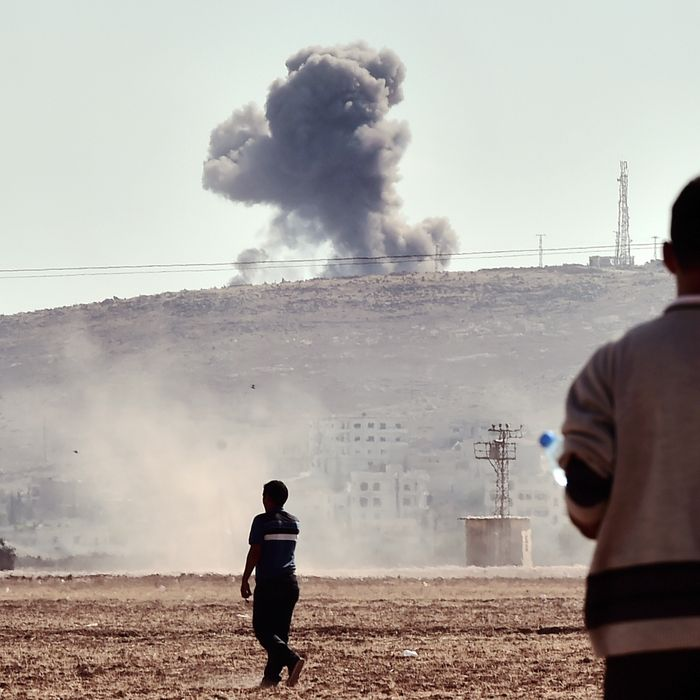People watch smoke rising from the Syrian town of Ain al-Arab, known as Kobane by the Kurds, after an air strike, on October 8, 2014 in the Turkish-Syrian border, in the southeastern village of Mursitpinar, Sanliurfa province. AFP PHOTO / ARIS MESSINIS (Photo credit should read ARIS MESSINIS/AFP/Getty Images)