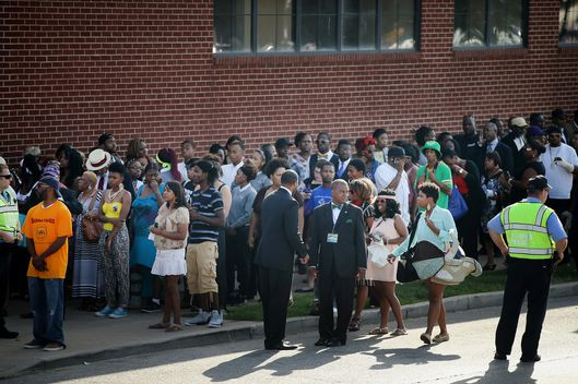 Guests wait in line to enter the Friendly Temple Missionary Baptist Church for the funeral of Michael Brown on August 25, 2014 in St. Louis, Missouri. Michael Brown, an 18 year-old unarmed teenager, was shot and killed by Ferguson Police Officer Darren Wilson in the nearby town of Ferguson, Missouri on August 9. His death caused several days of violent protests along with rioting and looting in Ferguson.