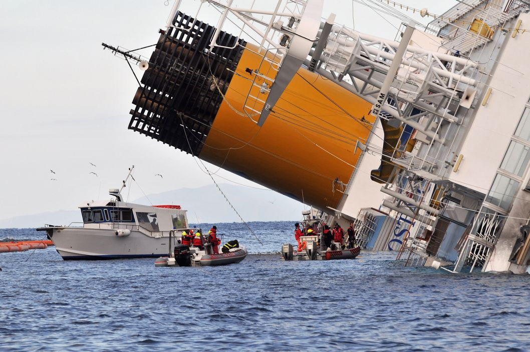 Rescuers work on the cruise ship Costa Concordia as lies stricken off the shore of the island of Giglio, on January 17, 2012 in Giglio Porto, Italy. More than four thousand people were on board when the ship hit a rock off the Tuscan coast.  At least 11 people have been confirmed dead and another 24 missing.