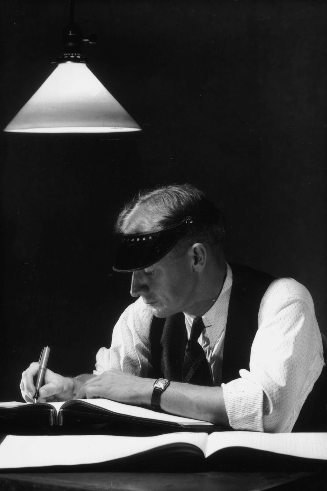 circa 1945:  A bookkeeper sits at a desk in the dark and writes in a ledger with a lamp hanging above him. He wears a visor, a vest, and shirt sleeves.  (Photo by Hulton Archive/Getty Images)