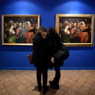 "Visitors compare two copies of the 16th century painting by Italian artist Lorenzo Lotto ""Christ and the adulteress"" as part of the exhibition ""Lorenzo Lotto and the artistic treasures of Loreto"" on show at the National museum of Castel Sant'Angelo in Rome, on February 2, 2015."