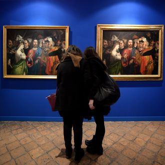 Visitors compare two copies of the 16th century painting by Italian artist Lorenzo Lotto