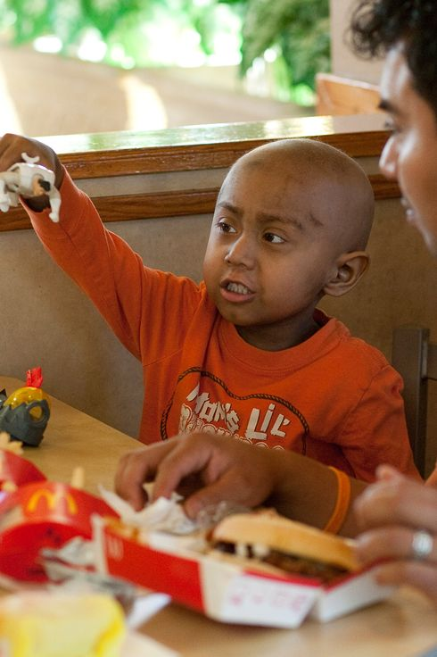 Five-year-old Andy Villatoro plays with a toy he received after ordering a Happy Meal at McDonald's as his father Carlos Villatoro (R) watches on November 3, 2010 in San Francisco, California.