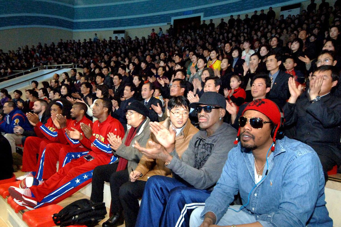 """In this image released by the Korean Central News Agency (KCNA) and distributed by the Korea News Service, former NBA star Dennis Rodman, second right in front row, visits a dolphin aquarium in Pyongyang in North Korea Friday, March 1, 2013.  Ending his unexpected round of basketball diplomacy in North Korea on Friday,  Rodman called leader Kim Jong Un an """"awesome guy"""" and said his father and grandfather were """"great leaders."""""""