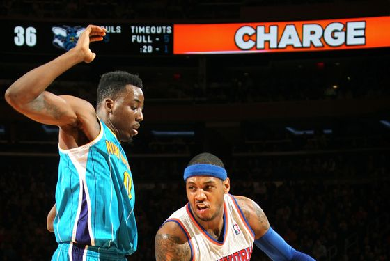 Carmelo Anthony #7 of the New York Knicks drives against Al-Farouq Aminu #0 of the New Orleans Hornets on January 13, 2013 at Madison Square Garden in New York City.