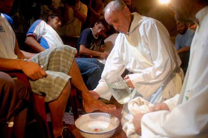 Pope Francis washing men's feet.