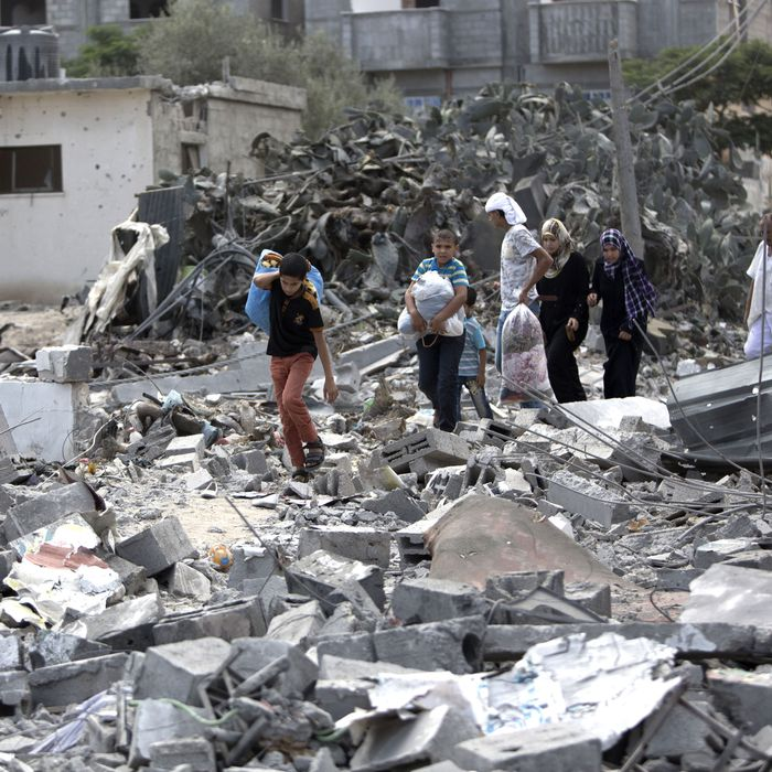 Palestinians carry their possessions as they walk on the rubble of buildings destroyed during the Israeli military offensive, close to the Rafah refugee camp, in southern Gaza Strip, on August 4, 2014. Civil defence workers and medics are searching the neighborhood looking for victims of the ongoing Israeli military operation which has killed some 1,829 Palestinians, mainly civilians. AFP PHOTO / MAHMUD HAMS (Photo credit should read MAHMUD HAMS/AFP/Getty Images)