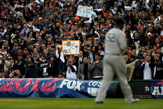 Fans of the Detroit Tigers cheer and hold up signs as CC Sabathia #52 of the New York Yankees walks back to the dugout after he was taken out of the game in the bottom of the fourth inning during game four of the American League Championship Series at Comerica Park on October 18, 2012 in Detroit, Michigan.