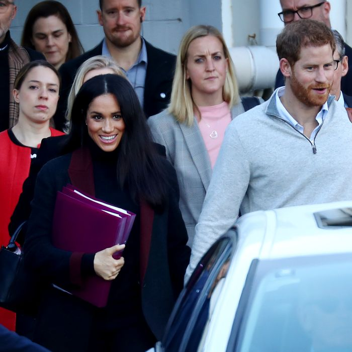 Meghan Markle (with binders) and Prince Harry in Sydney.