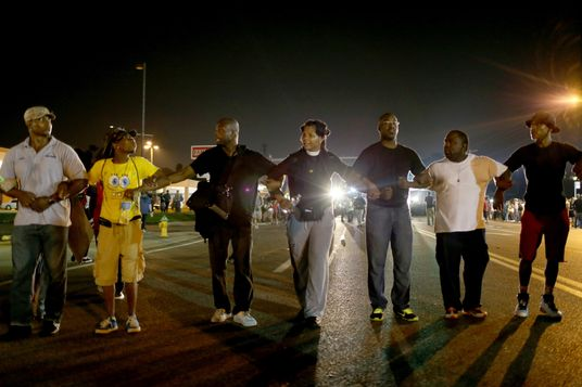 FERGUSON, MO - AUGUST 18:  Demonstrators protesting the shooting death of Michael Brown walk down the street on August 18, 2014 in Ferguson, Missouri. Protesters have been vocal asking for justice in the shooting death of Michael Brown by a Ferguson police officer on August 9th.  (Photo by Joe Raedle/Getty Images)