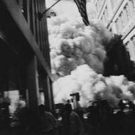 Smoke and debris rushes through the Wall Street area near Trinity Church, after the first tower collapses during the World Trade Center attack.